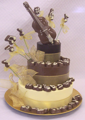 a picture of milk chocolate violin on three chocolate tiers, decorated with white chocolate and musical notes