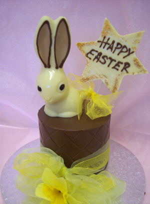 a picture of one white chocolate bunny rabbit on a milk chocolate tier.  Decorated with yellow flowers and mounted on a silver display disc.