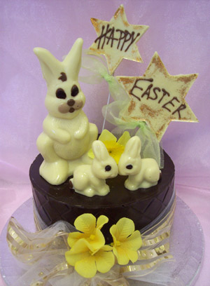 a picture of three white chocolate bunny rabbits on a milk chocolate tier.  Decorated with yellow flowers and mounted on a silver display disc.