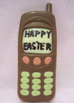 a picture of a milk chocolate mobile phone decorated with white and coloured chocolate. Display screen says 'happy easter'