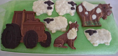 a picture of a milk chocolate farm animals and tractor, decorated with white and dark chocolate