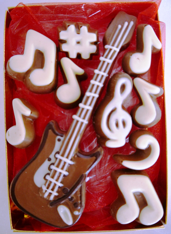 a picture of a milk chocolate guitar decorated with white and dark chocolate
