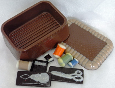 a picture of a milk chocolate sewing kit decorated with milk, white, dark, and coloured chocolate