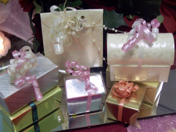 a picture of seven small wedding favours boxes, differently coloured and each tied with ribbon
