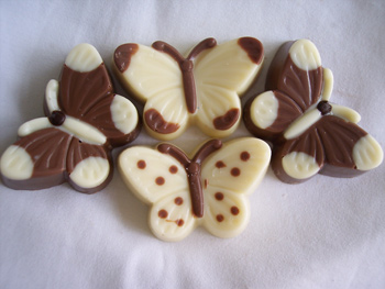 a picture of four chocolate butterflies, decorated with milk and white chocolate