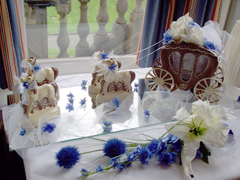 a picture of a milk chocolate wedding carriage, with white chocolate horses, decorated ribbon and blue flowers
