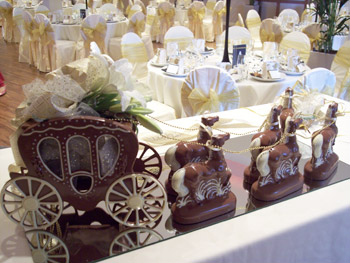 a picture of a milk chocolate wedding carriage and horses, decorated with ribbon, flowers and a gold rein