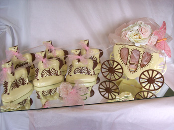 a picture of a white chocolate wedding carriage and horses, decorated with pink ribbon and butterfly