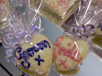 a picture of two small chocolate love hearts, one with 'Groom' and one with 'Bride' written in coloured chocolate.