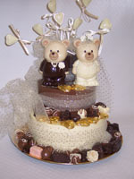milk and white chocolate wedding teddies decorated with love hearts and ribbon on a chocolate tier