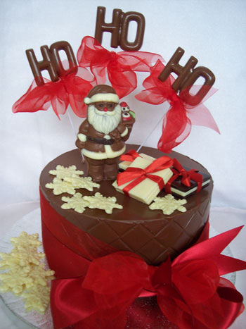 a picture of a milk chocolate Father Christmas on a chocolate tier, decorated with coloured chocolate and red ribbon.  Chocolate letters reads 'Ho Ho Ho'