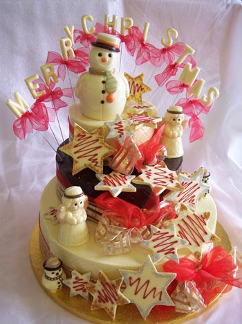 a picture of a white chocolate snowman with Angels decorated with coloured chocolate, snowflakes and red ribbon on chocolate tiers.  Chocolate letters reads 'Merry Christmas'
