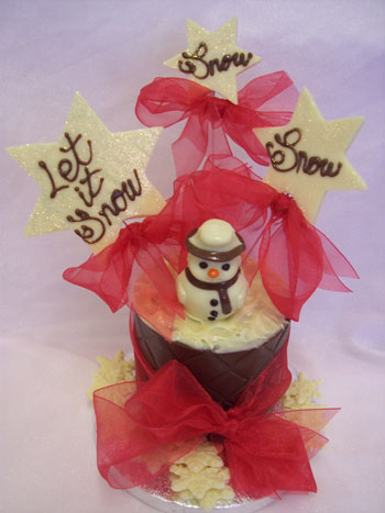 a picture of a white chocolate snowman decorated with coloured chocolate and red ribbon on a chocolate tier.  Large chocolate snowflakes reads 'Let it Snow'